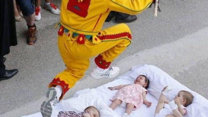 """Hombres se visten de """"diablo"""" y saltan sobre bebés para purificarlos"""
